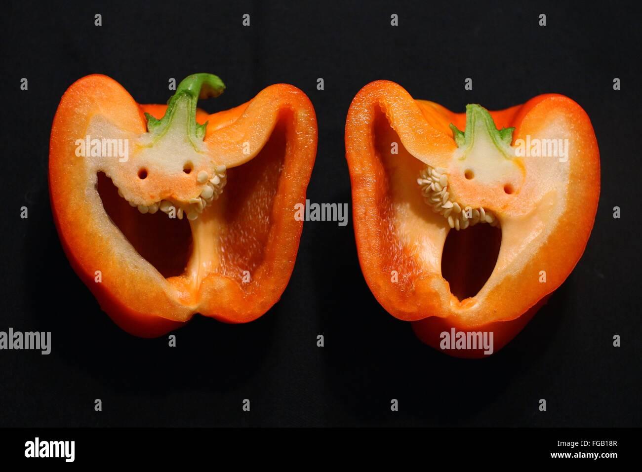 Couper les poivrons orange sur fond noir Photo Stock