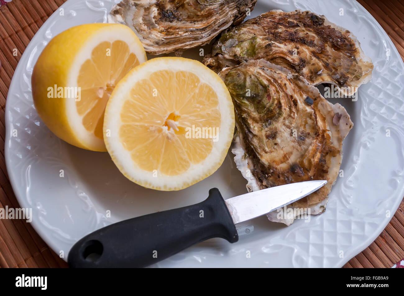 La préparation des mollusques pour la consommation, l'ouvrir, sur l'arrière-plan de citron dans Photo Stock