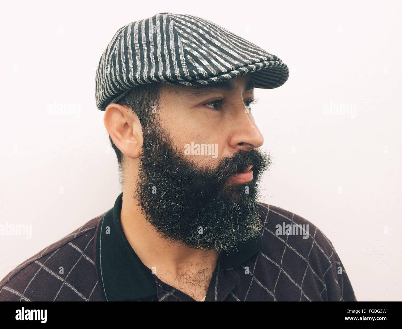 Vue latérale d'homme mûr avec Beard Wearing Hat Against White Background Photo Stock