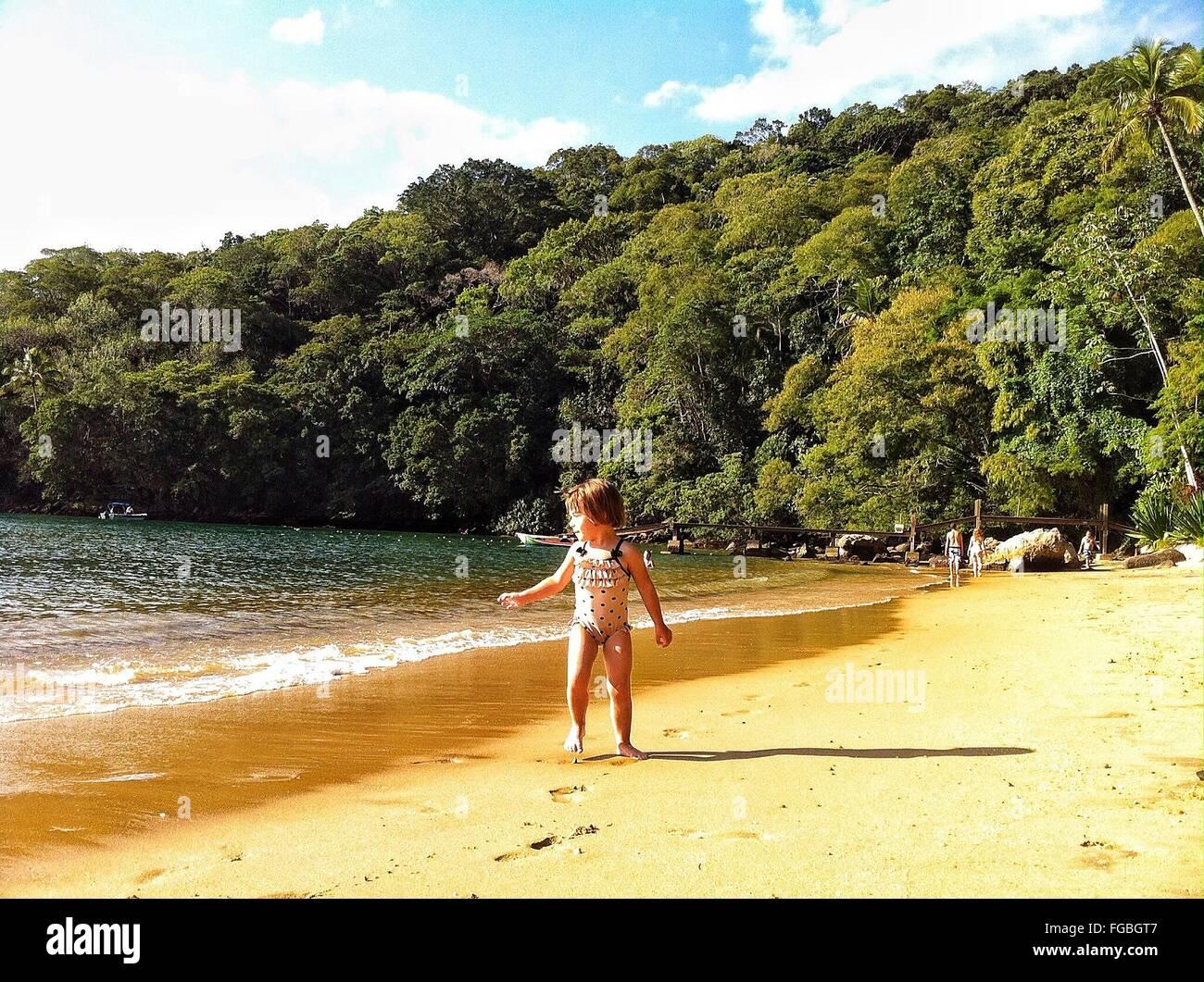 Curieux Girl standing on shore contre des arbres Photo Stock