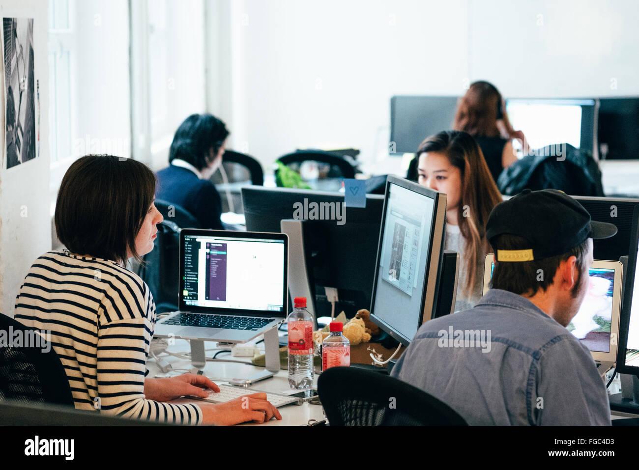 Les personnes travaillant sur des ordinateurs au bureau Photo Stock