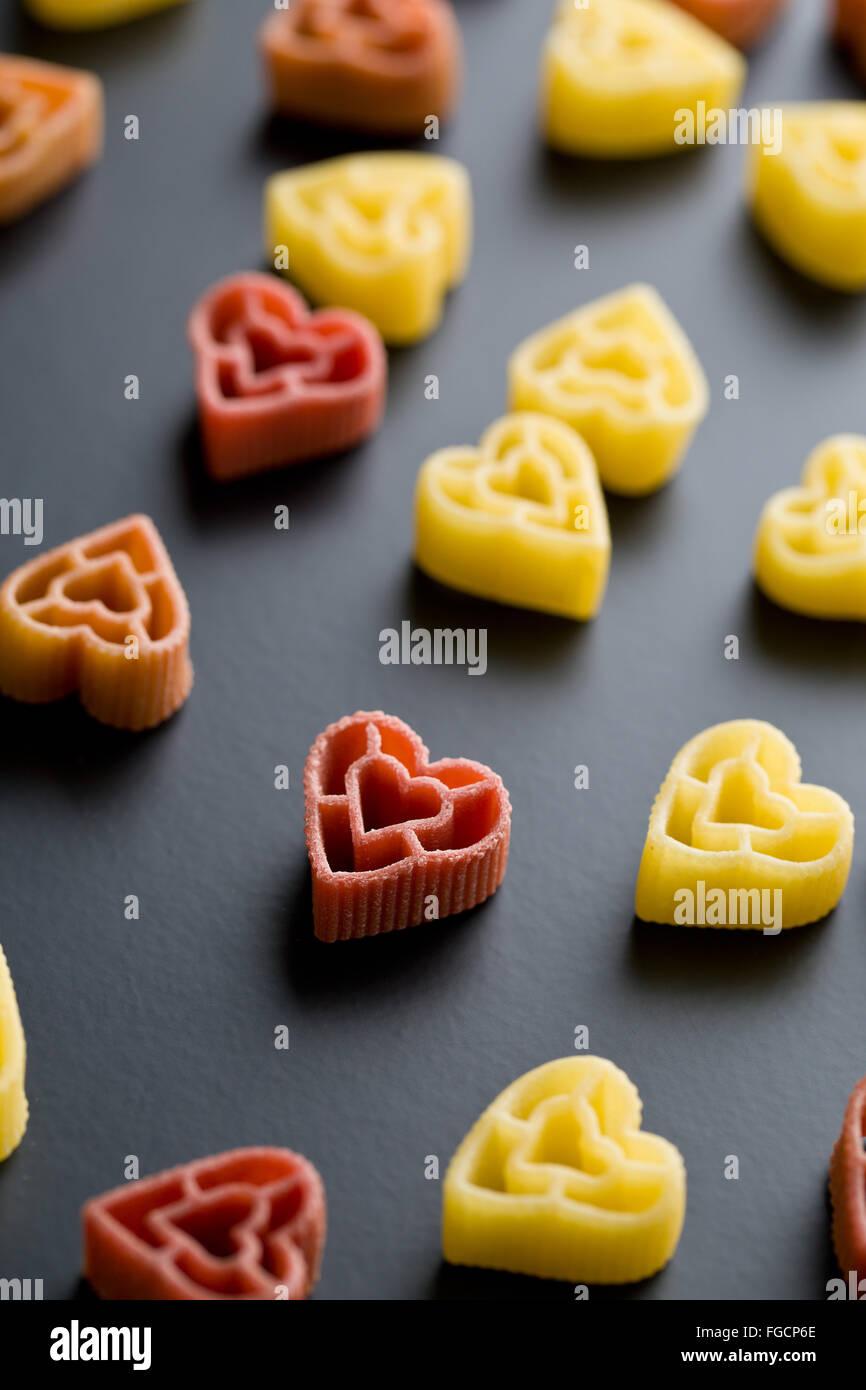 Les pâtes en forme de coeur sur fond noir Photo Stock