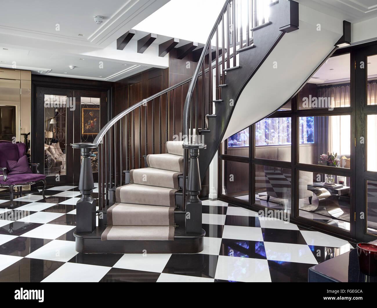 escalier en bois courbé avec carrelage noir et blanc montrant un