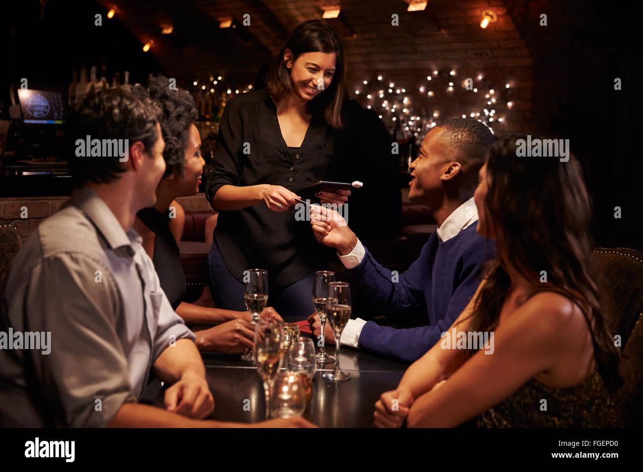 Serveuse prend le paiement de facture de restaurant sur tablette numérique Photo Stock