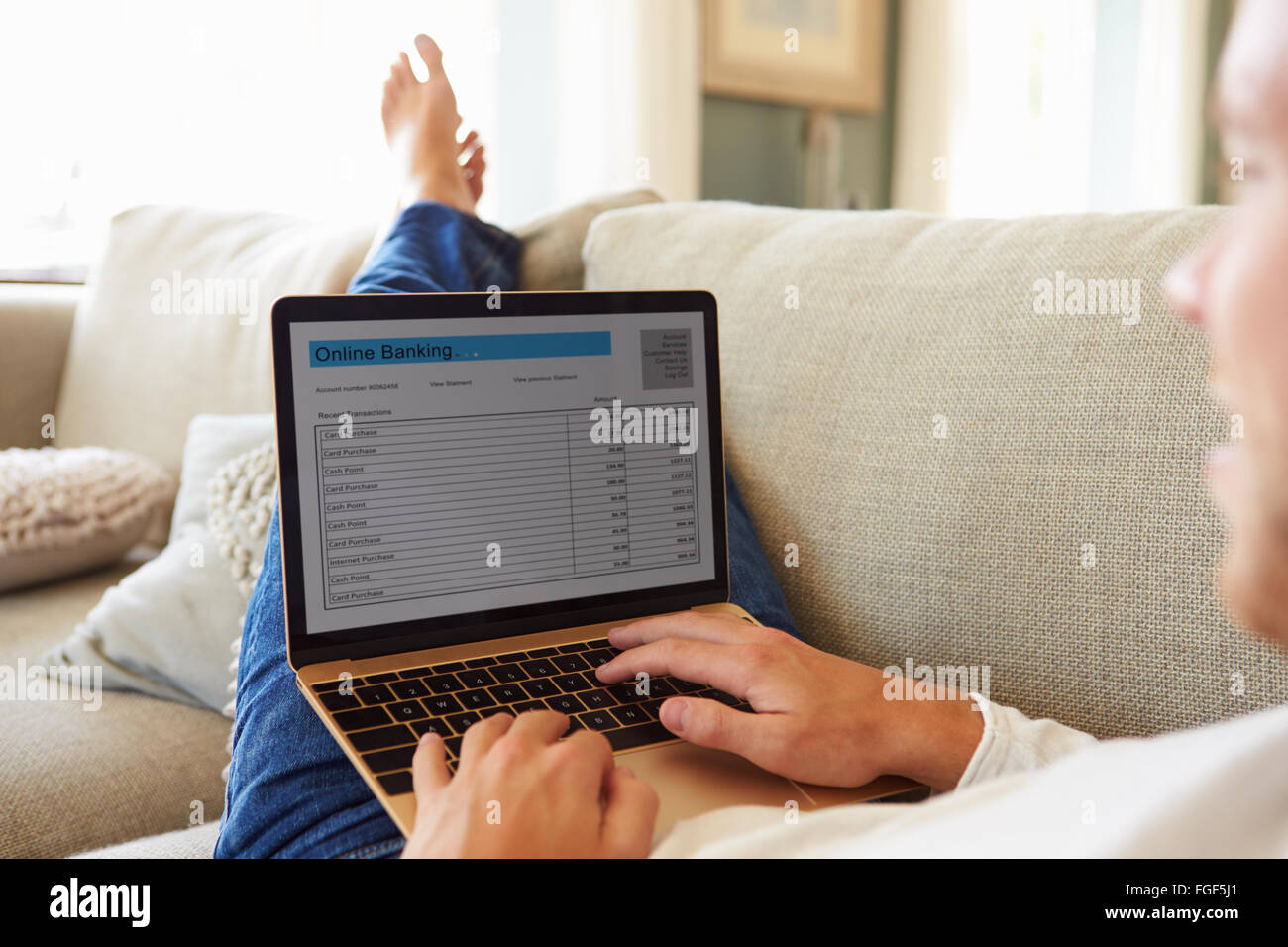 Man Relaxing On Sofa Using Internet Banking on laptop computer Photo Stock