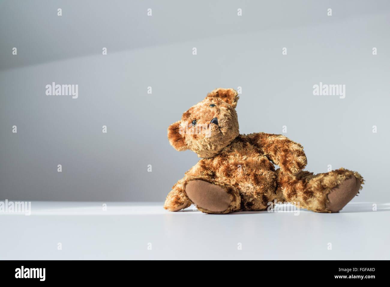 Ours en peluche brun assis sur le plancher incliné sur un côté Photo Stock