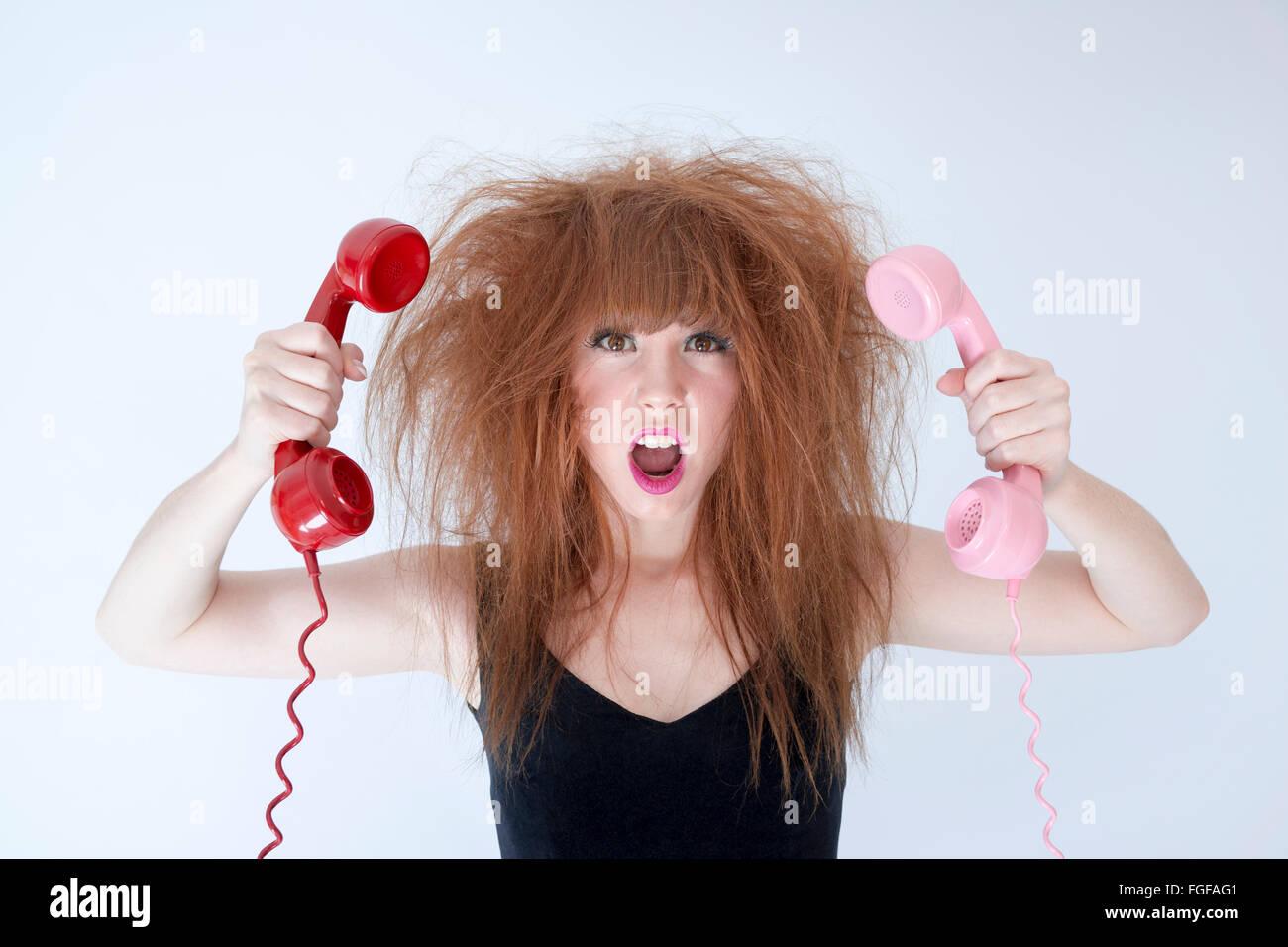 Femme aux cheveux en désordre tenant deux cris téléphones rétro Photo Stock