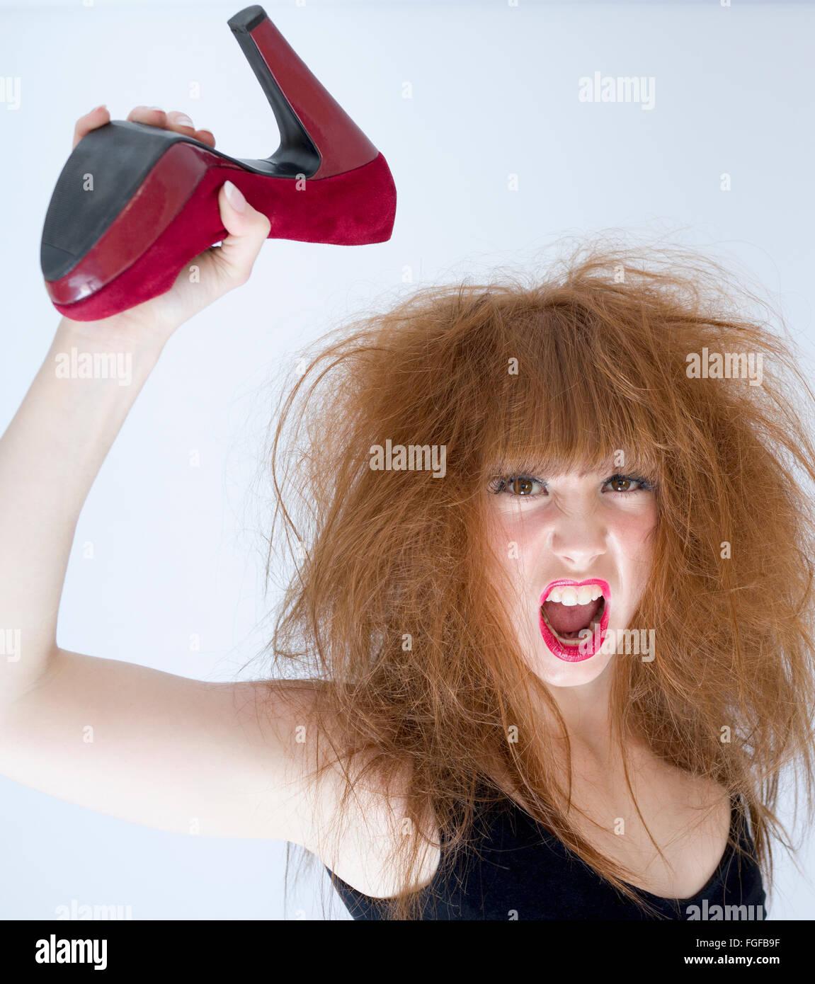 Femme aux cheveux en désordre tenant une chaussure haut talon en daim rouge dans l'air sur le point de frapper, Banque D'Images