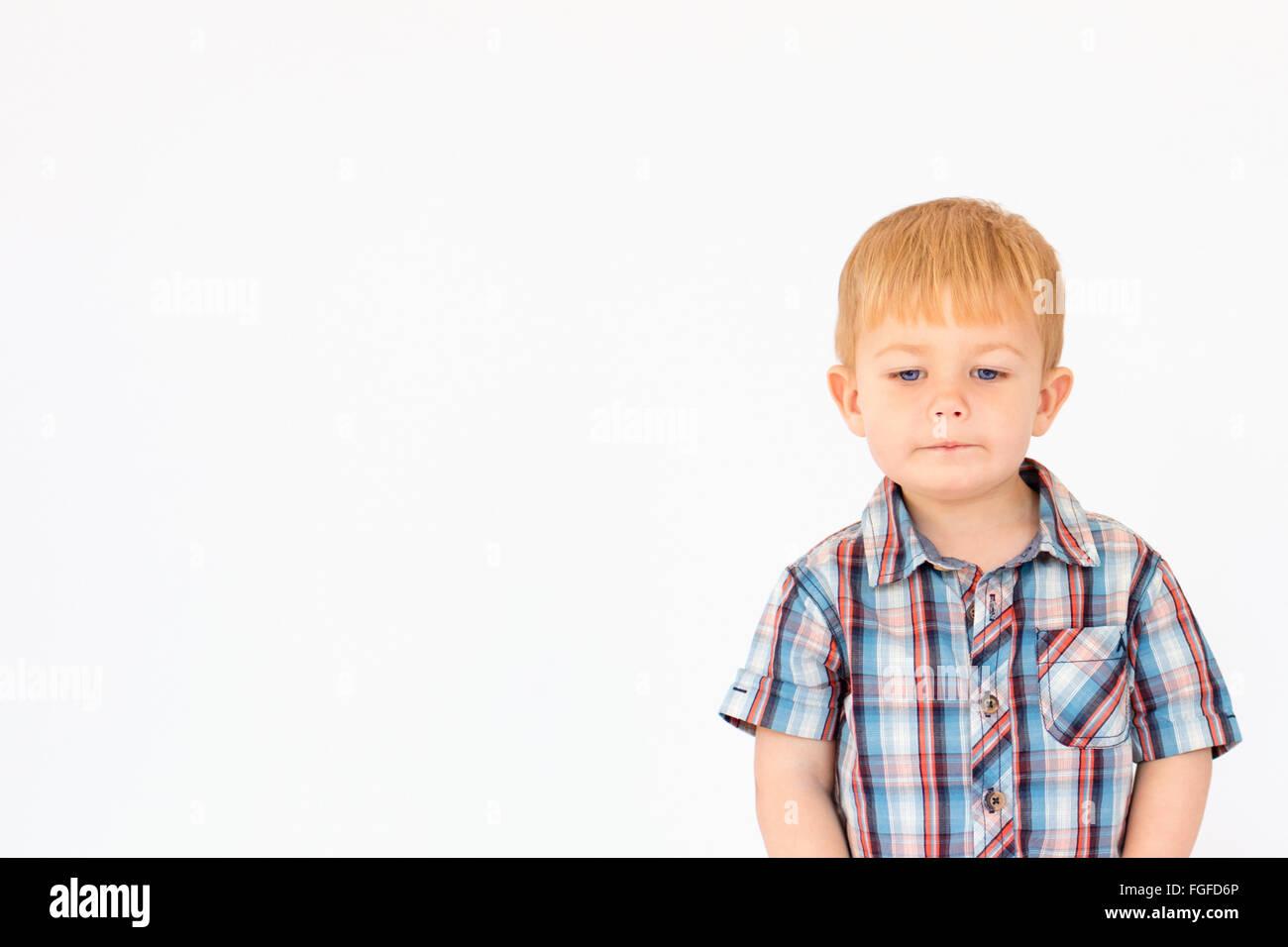 Portrait d'un jeune garçon debout sur un fond blanc. Photo Stock
