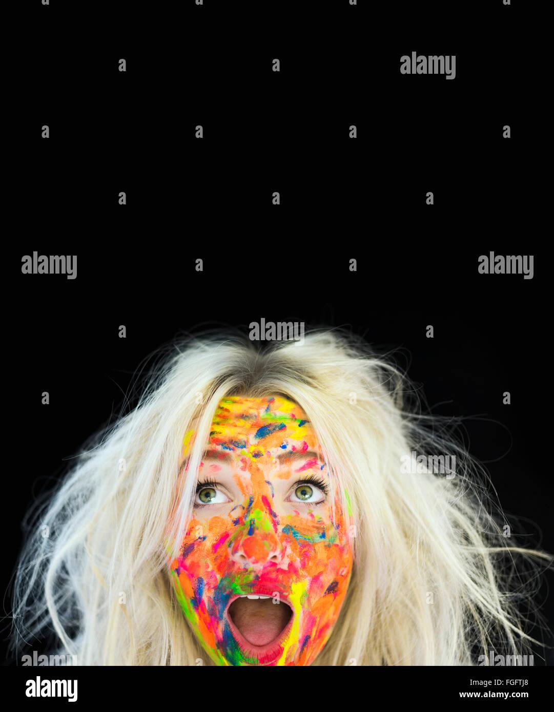 Femme aux cheveux blonds en désordre et le visage couvert de peinture multicolores avec une expression surprise Photo Stock