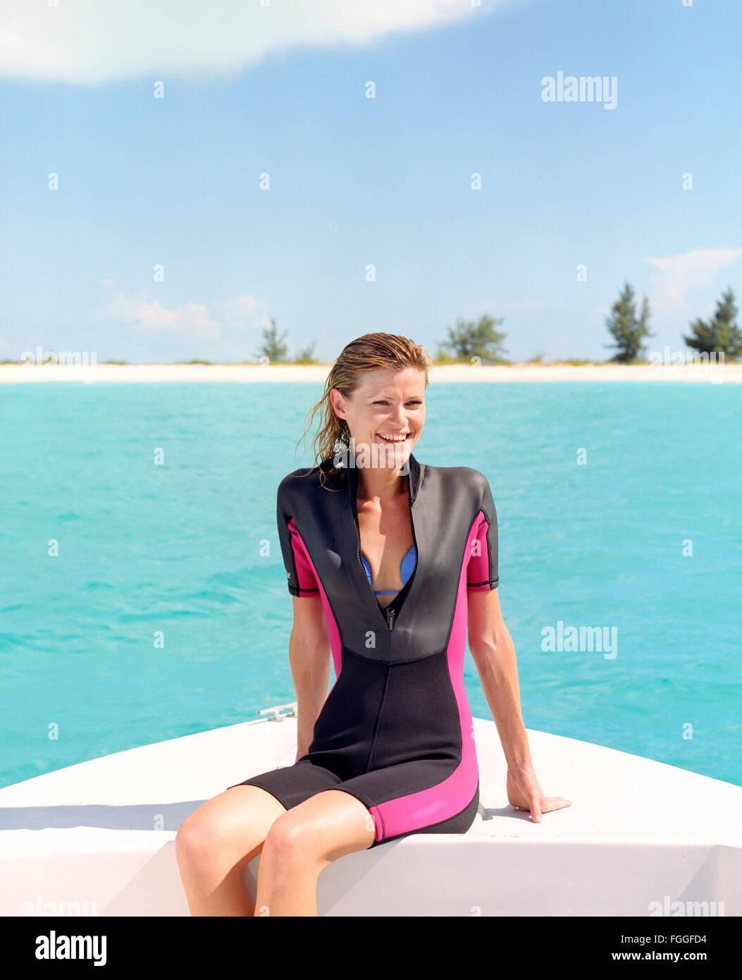 Une jeune femme sites sur un bateau avant la plongée.Providenciales, Îles Turques et Caïques. Dans Photo Stock