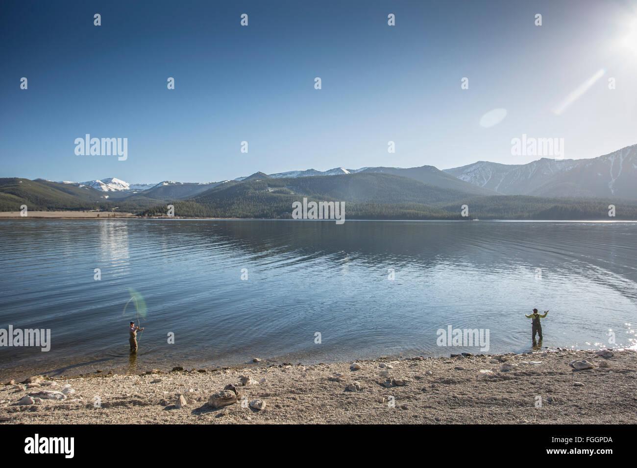 Deux femmes dominante de la rive, tandis que la pêche à la mouche sur le lac Hebgen du Montana. Photo Stock
