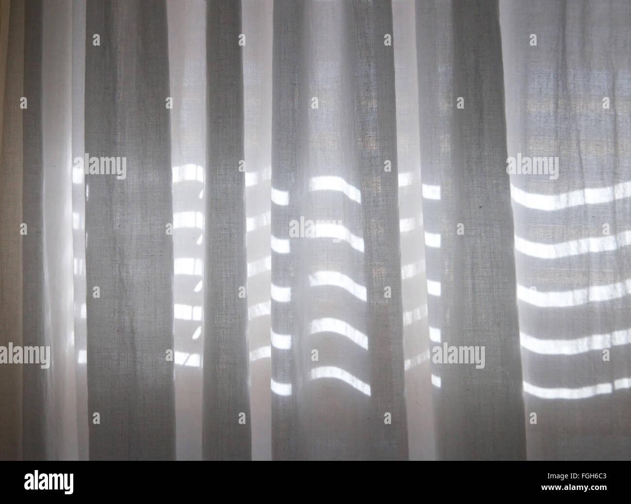 Close up de voilages blancs avec des bandes horizontales de la lumière du soleil montrant à travers des Photo Stock