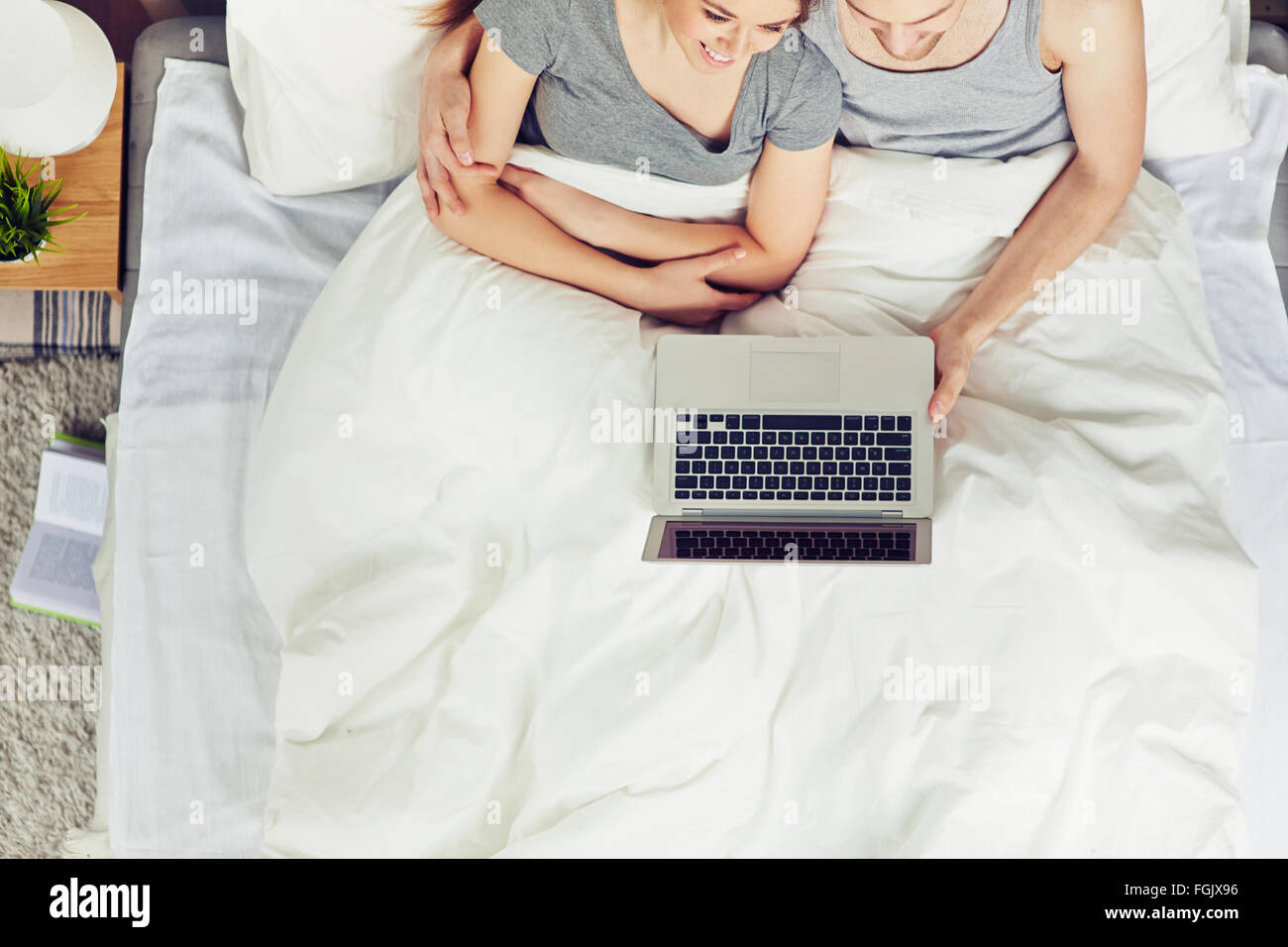 Young man and woman with laptop networking together in bed Banque D'Images