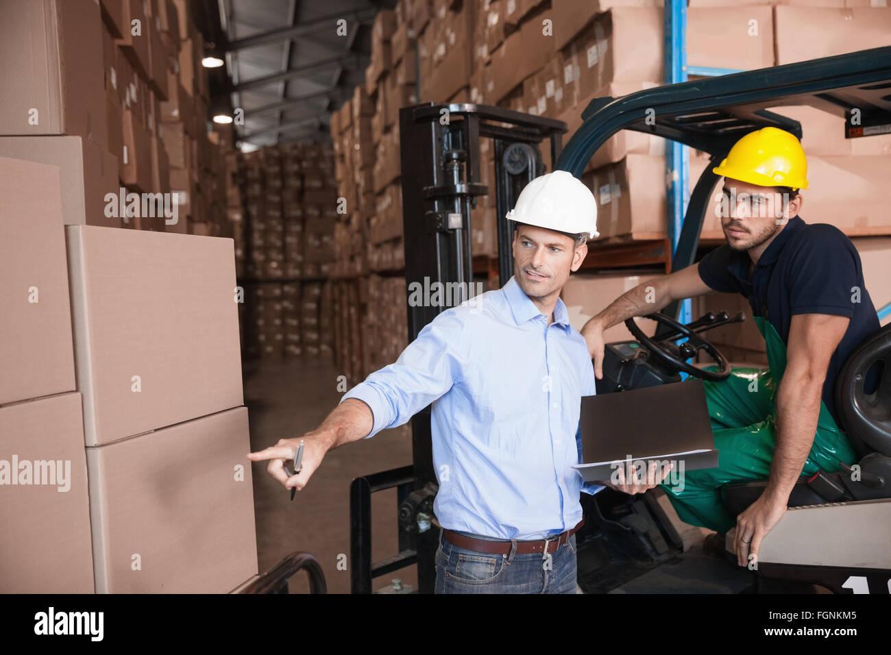 Warehouse Manager parlant avec conducteur de chariot élévateur Photo Stock