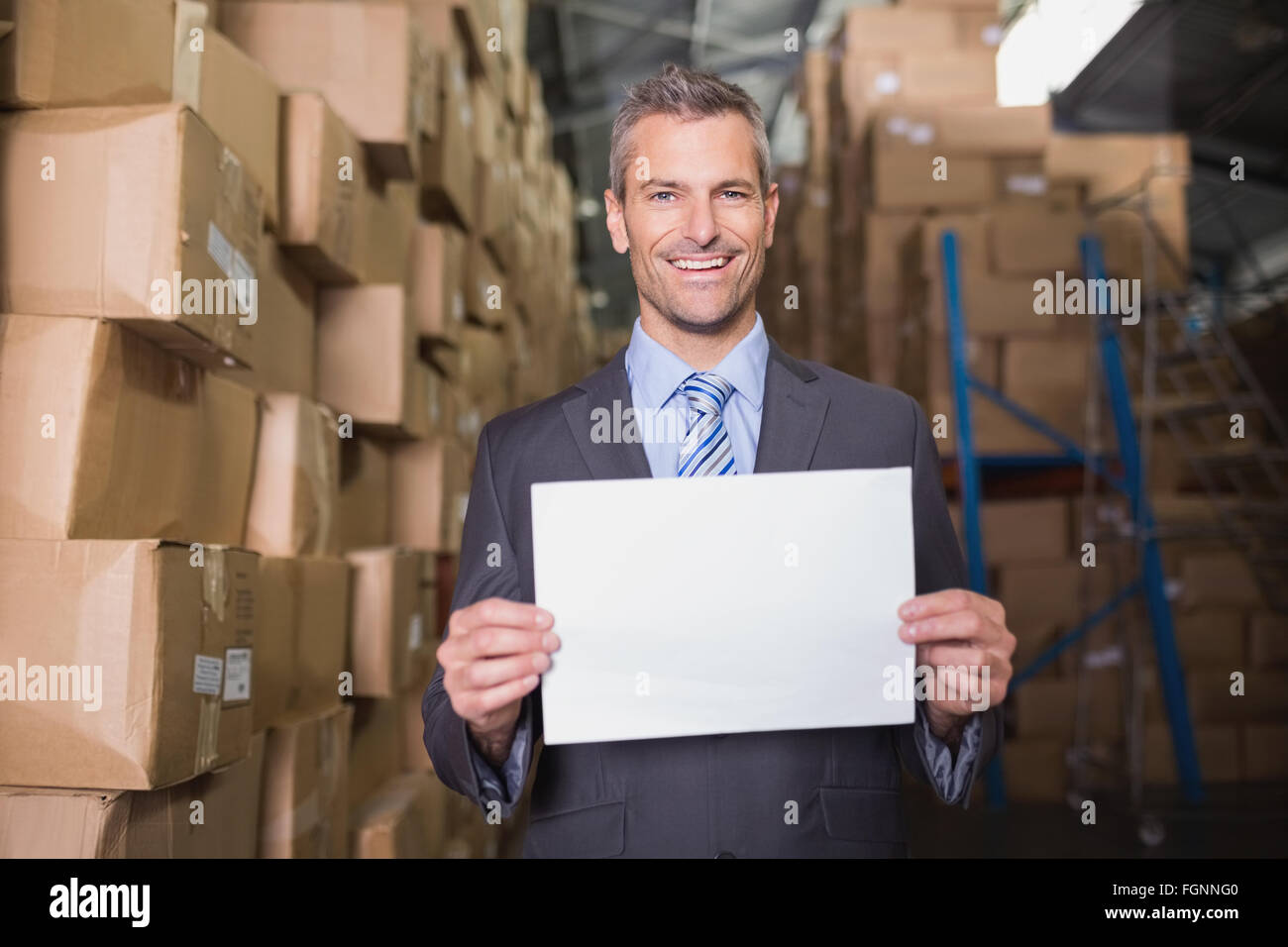 Manager holding blank board in warehouse Photo Stock