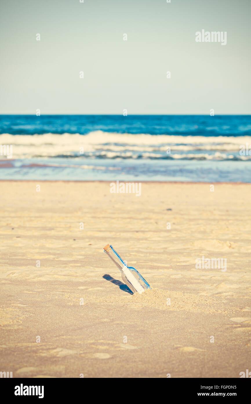 Les photos traitées d'une bouteille avec lettre sur plage, faible profondeur de champ. Photo Stock