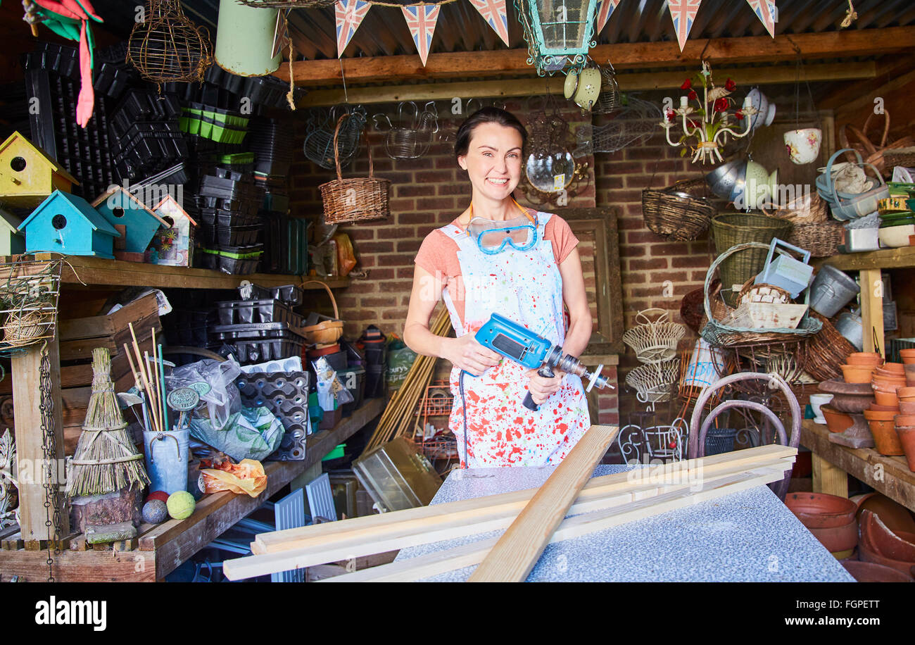 Portrait smiling woman with power sander en atelier Photo Stock