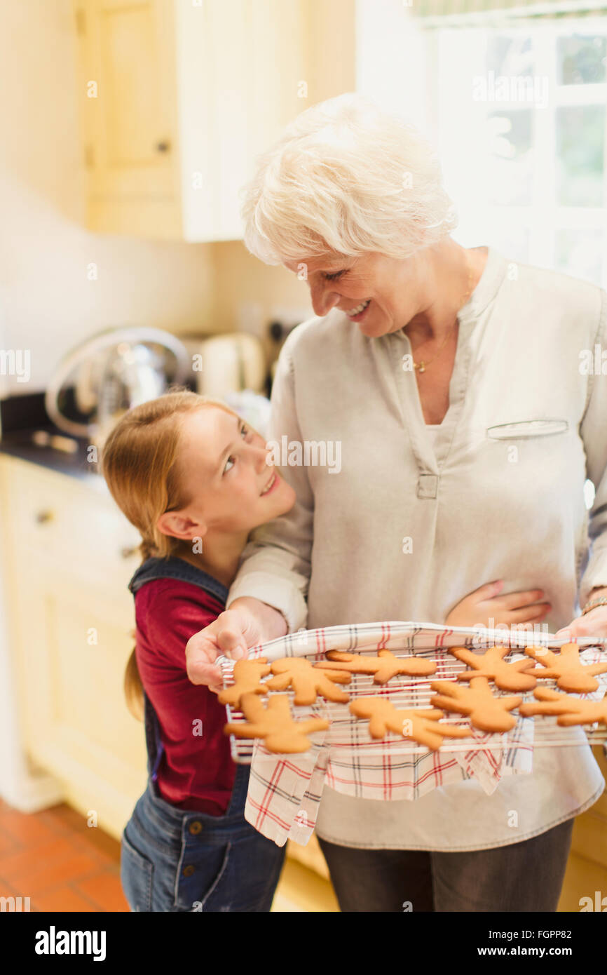 Granddaughter hugging grand-mère baking gingerbread cookies Photo Stock