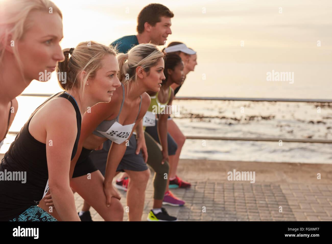Porteur debout sur la ligne au départ d'une course. Groupe de jeunes de la formation pour le marathon course sur Banque D'Images
