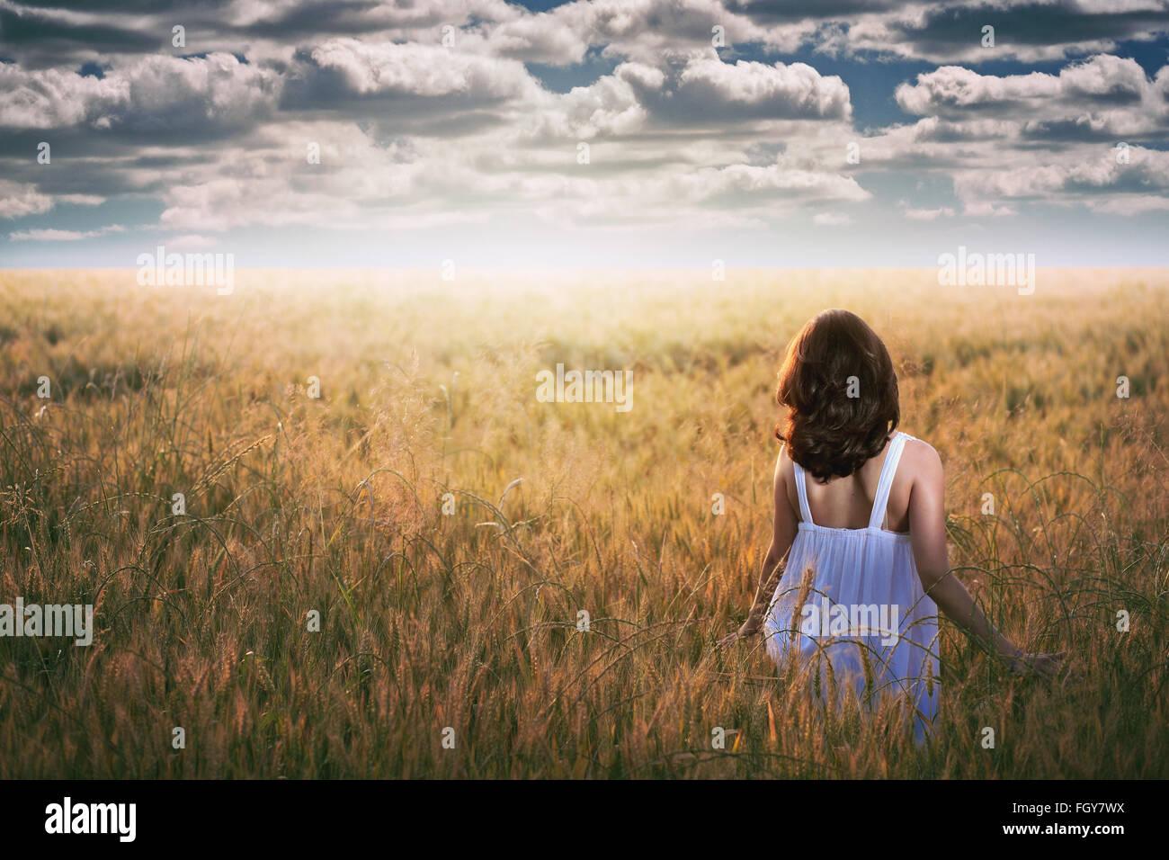 Femme regardant fixement un ciel dramatique dans un champ d'or . La lumière au coucher du soleil Photo Stock