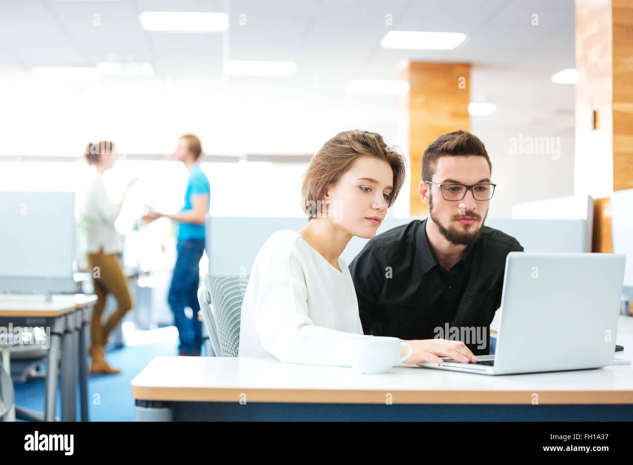 L'accent grave jeune homme et femme assise et travailler avec laptop in office Photo Stock