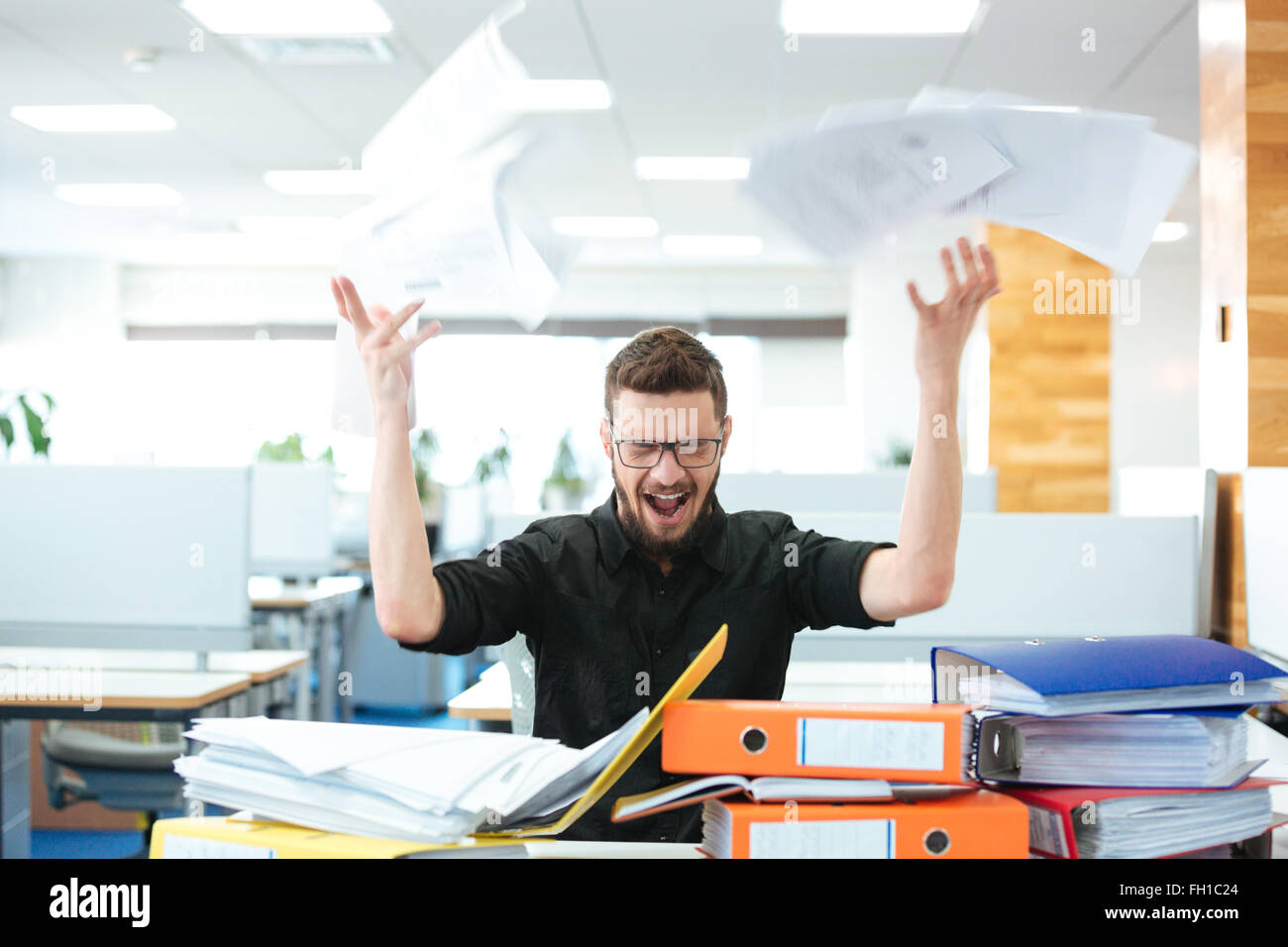 Angry businessman assis à la table et de crier in office Photo Stock