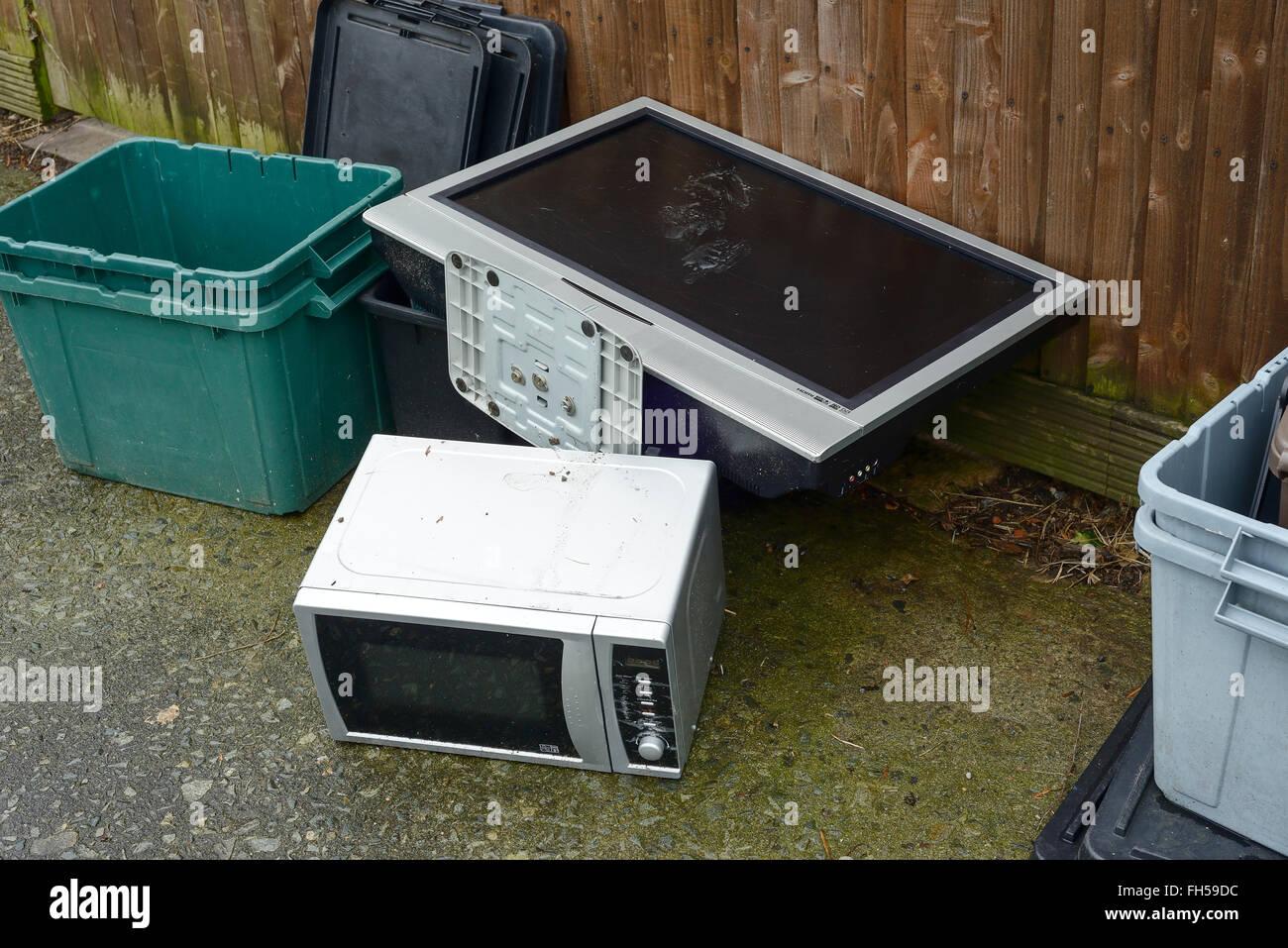 Une vieille télévision et un four à micro-ondes four déversés sur un trottoir Photo Stock