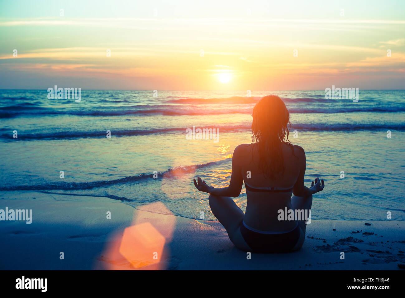 Silhouette femme yoga sur la plage au coucher du soleil. Photo Stock