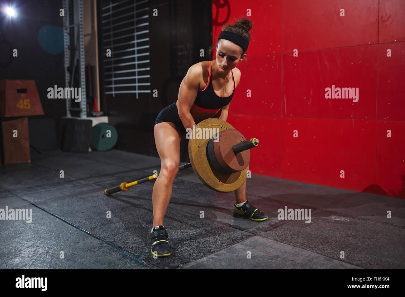 Une jeune femme avec des haltères lourds de la formation en salle de sport Photo Stock