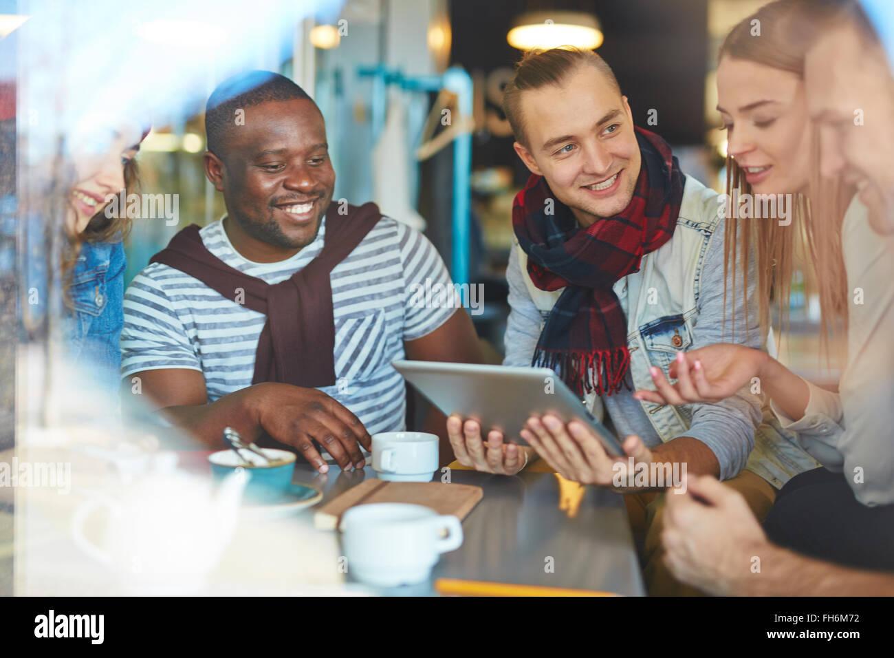 Sympa les gars et les filles de réseaux et de discuter des données dans cafe Photo Stock
