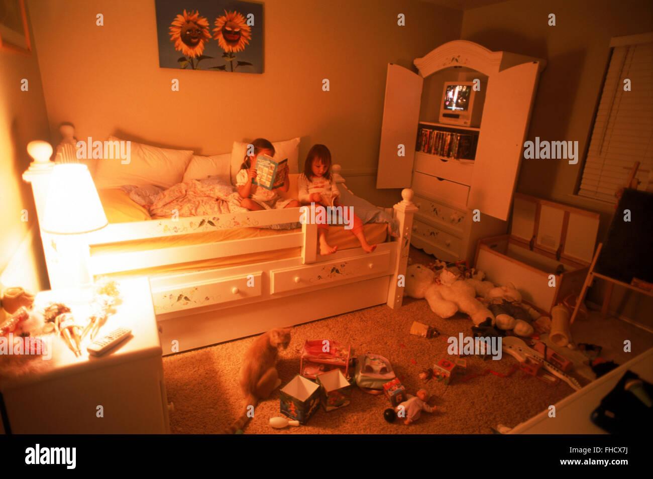 Deux jeunes filles dans la chambre au milieu de la mer malpropre toys Photo Stock