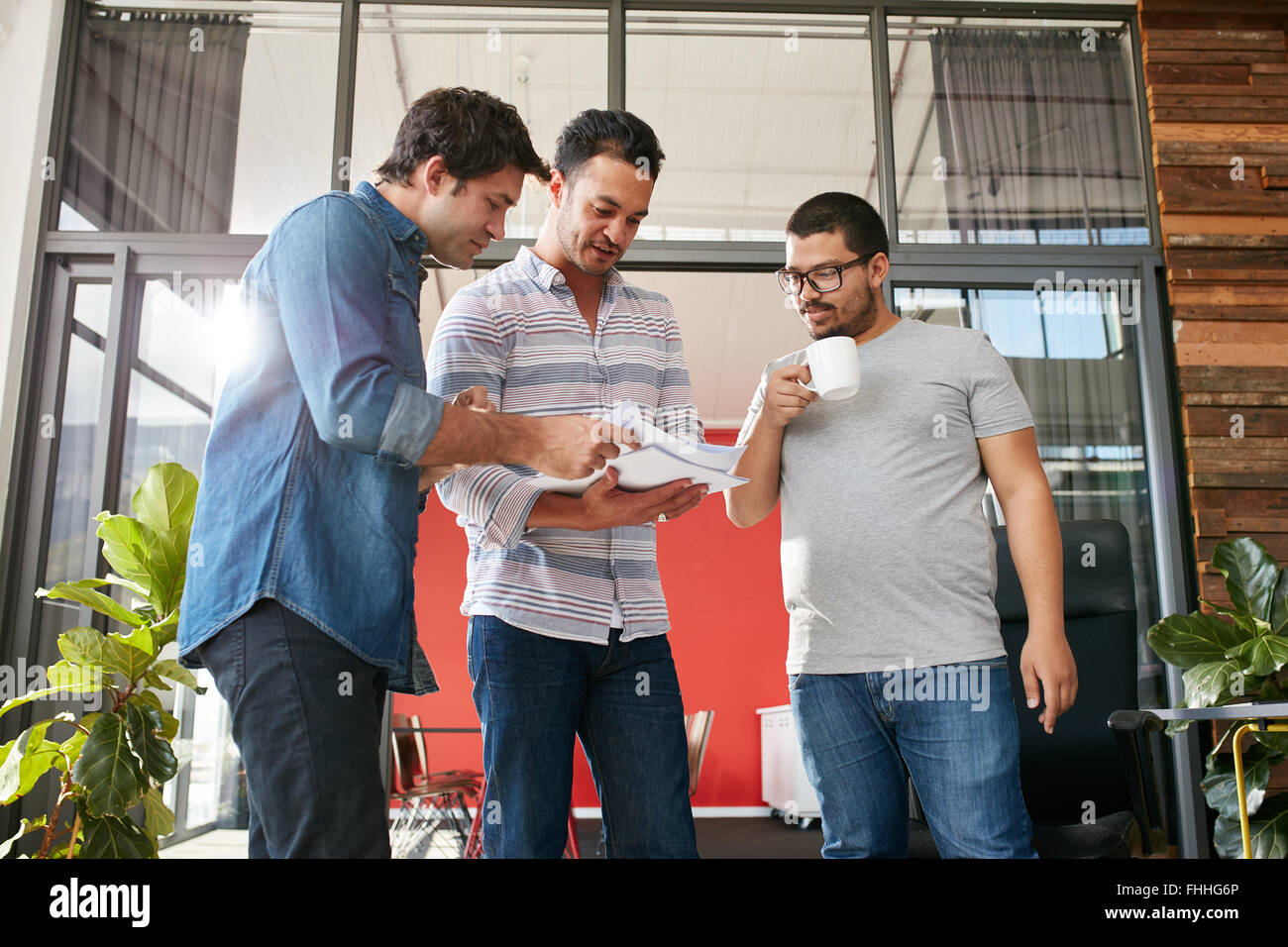 Groupe de businesspeople discussing paperwork in office. Trois jeunes hommes Réunion de bureau. Photo Stock
