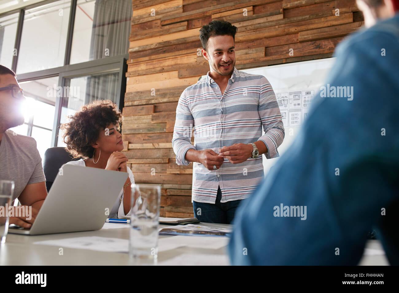 Portrait de jeune homme avec des collègues ayant séance dans la salle de conférence. Groupe diversifié Photo Stock