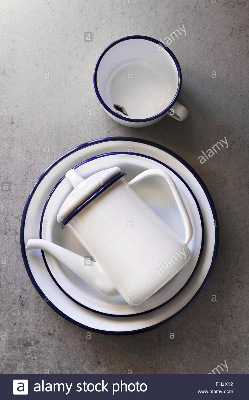 L'émail blanc Vintage cuisine, assiettes, tasse et une théière sur un conseil de cuisine.vue Photo Stock