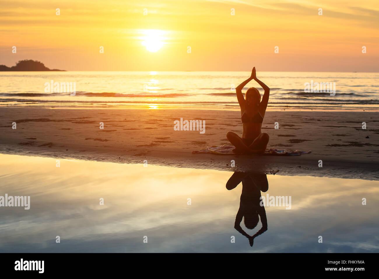 Silhouette de femme assise sur la plage pendant un beau coucher de soleil, avec reflet dans l'eau. Photo Stock