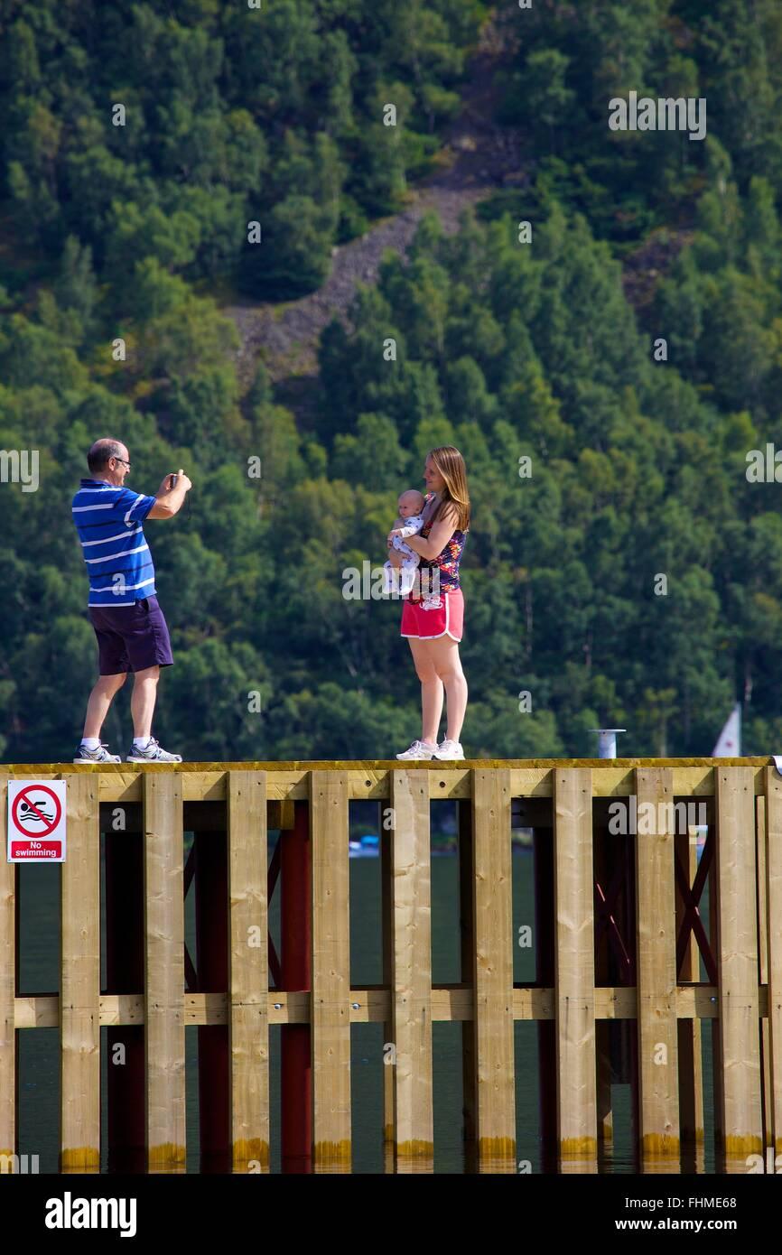 Parc National de Lake District. Man taking photo de sa femme et son bébé avec smart phone sur une jetée Photo Stock