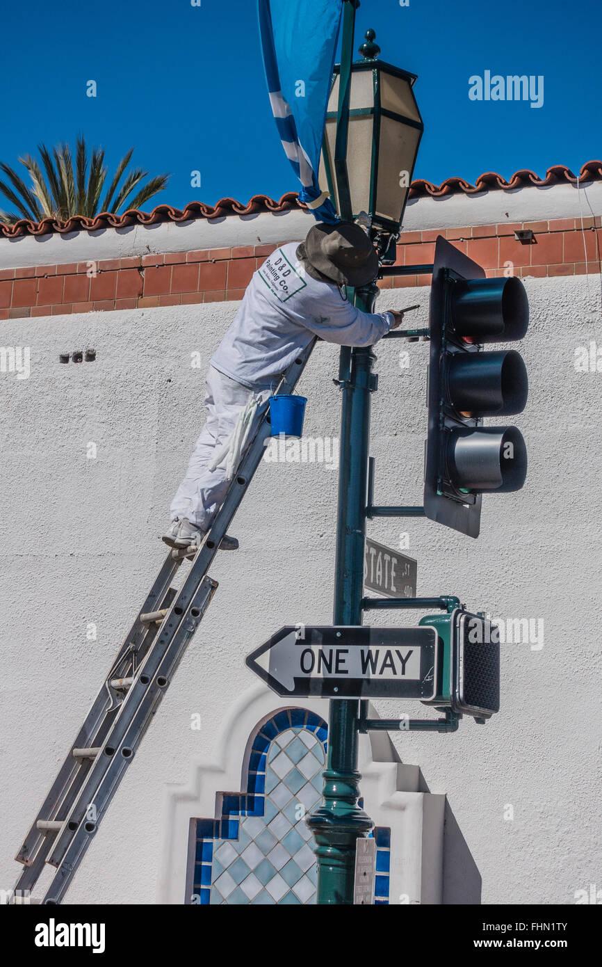 Un homme se tient sur un peintre hispanique de bain au-dessus de son vieux chiffon qu'il peint un feu de mât. Photo Stock