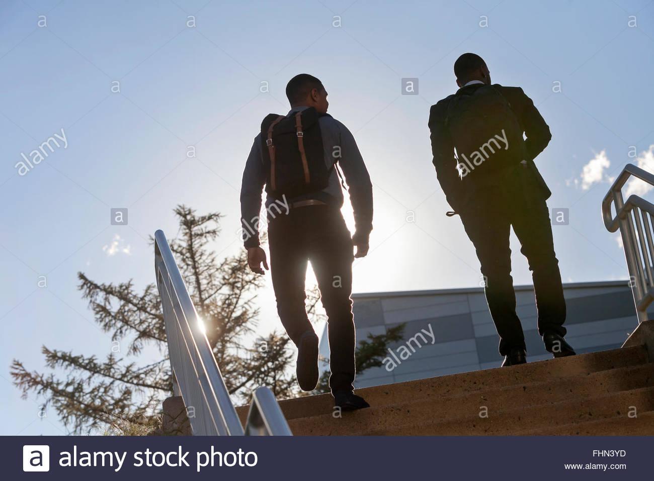 Deux jeunes hommes à monter escaliers extérieurs dans une silhouette. Photo Stock