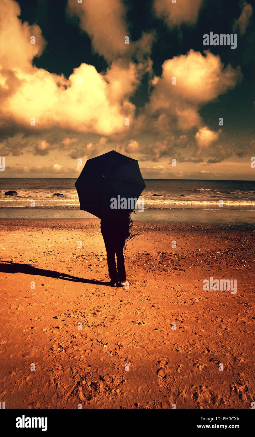 Femme avec parasol sur la plage Photo Stock