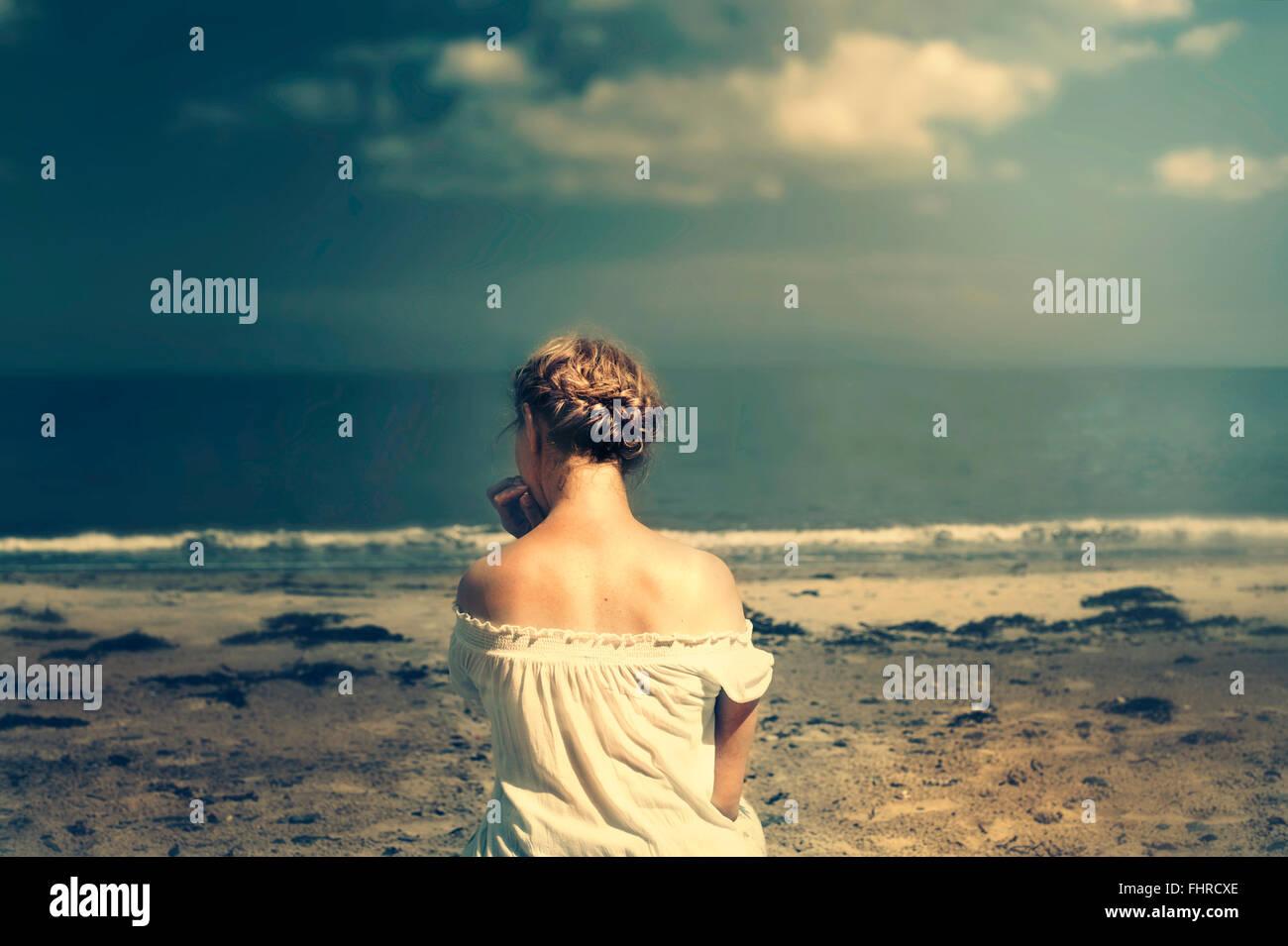 Jeune femme assise sur la plage Photo Stock