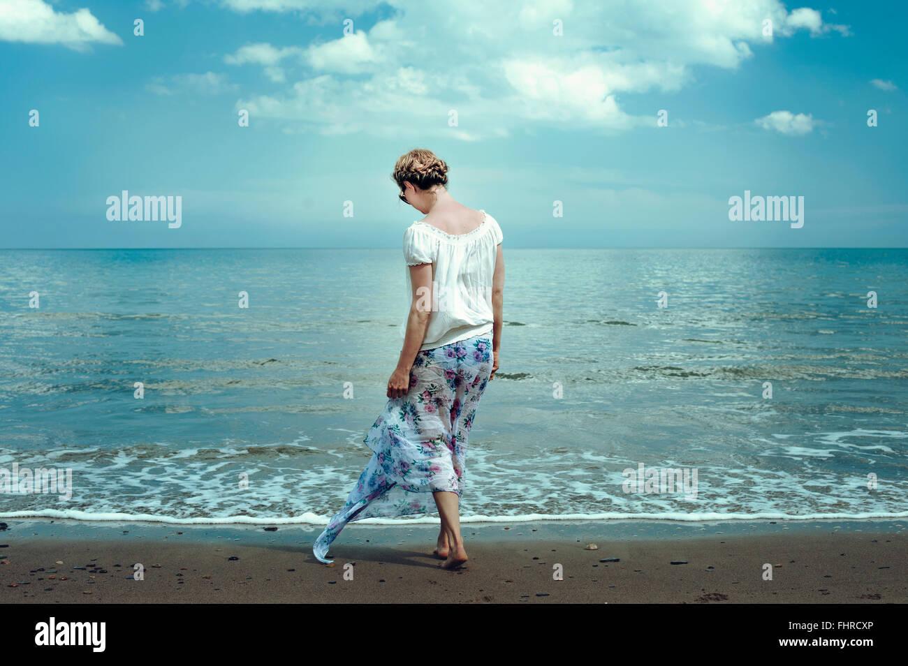 Jeune femme marche sur la plage Photo Stock