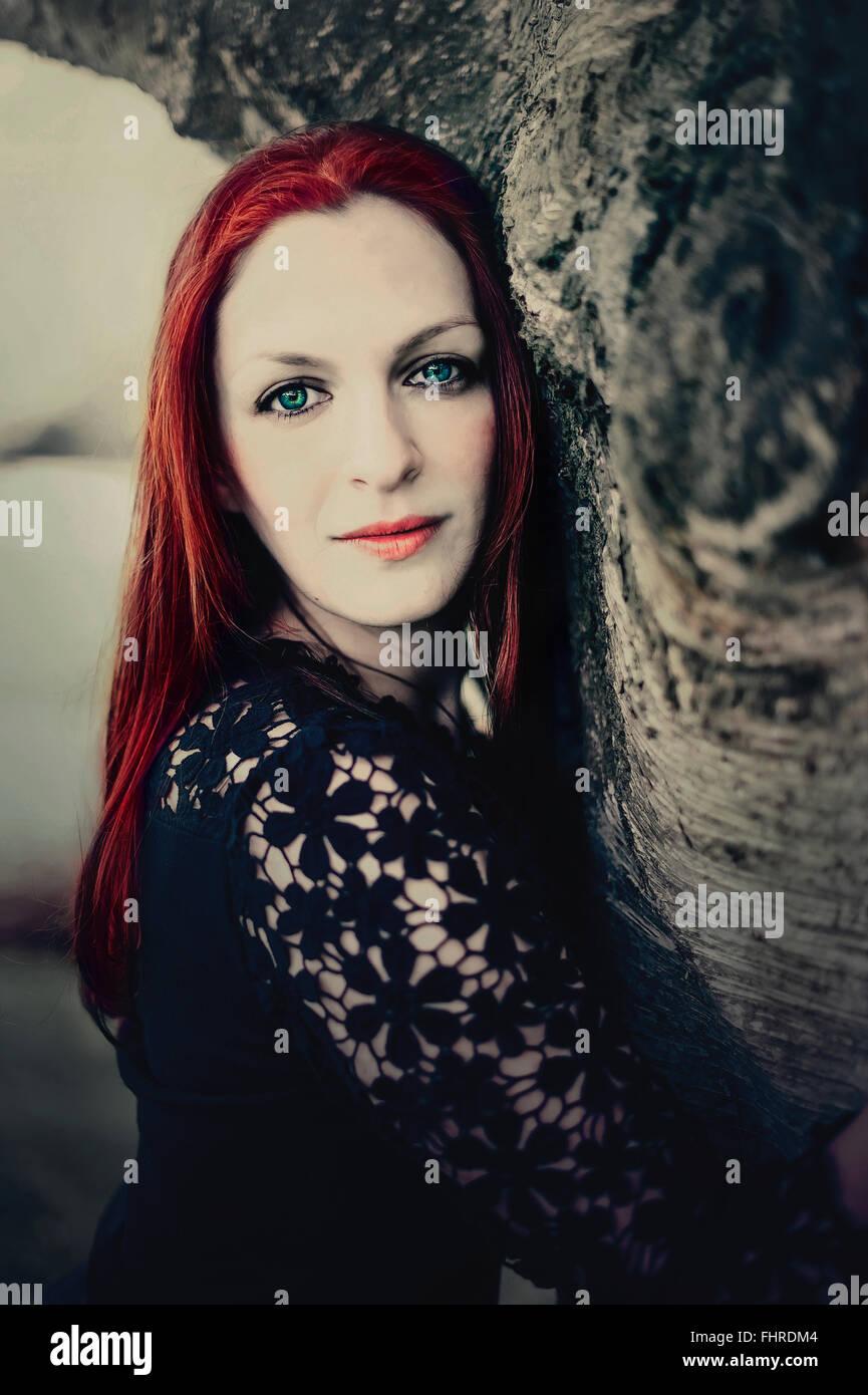 Portrait de la femme de cheveux rouge par l'arbre Banque D'Images