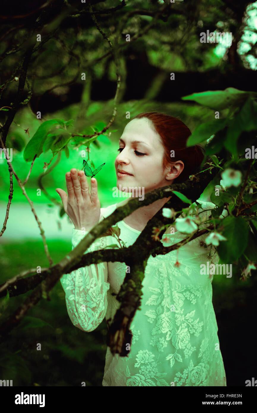 Jeune femme dans la forêt tenant un papillon Photo Stock