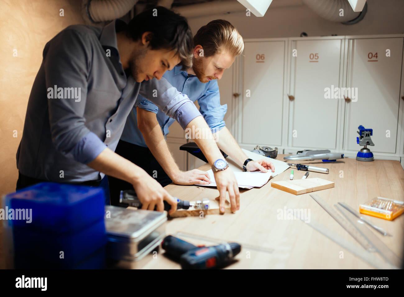 Deux designers qui travaillent ensemble en atelier avec des outils de précision Photo Stock