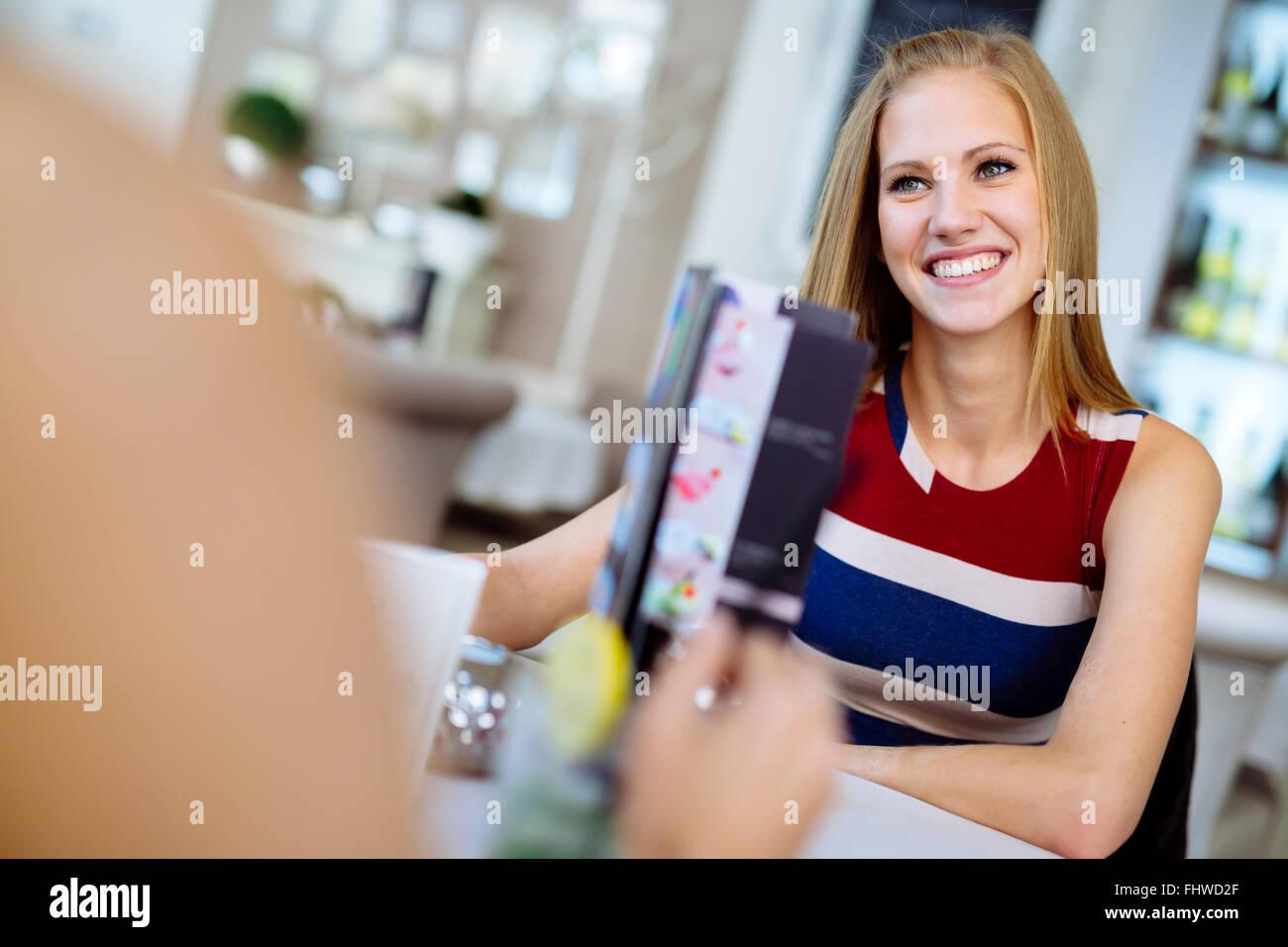 Des femmes qui parlent dans le restaurant tout en profitant de leurs boissons alcoolisées Banque D'Images