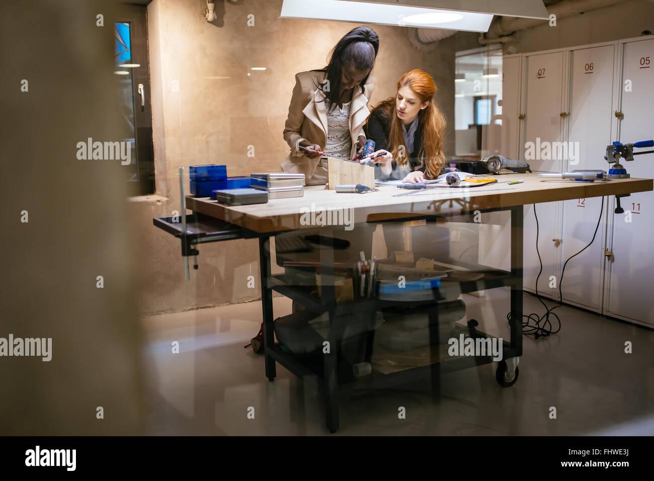 Les personnes qui travaillent dans l'atelier belle moderne avec du matériel professionnel à portée Photo Stock