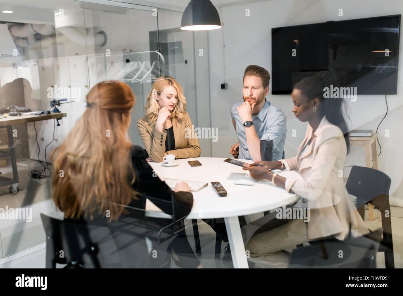 Les gens d'affaires réunion du conseil d'office moderne tout en étant assis à table ronde Photo Stock