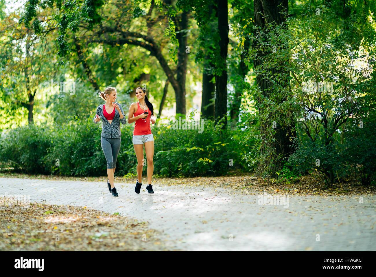 Les femmes sportives en jogging park et à l'écoute de musique au moyen d'écouteurs Photo Stock