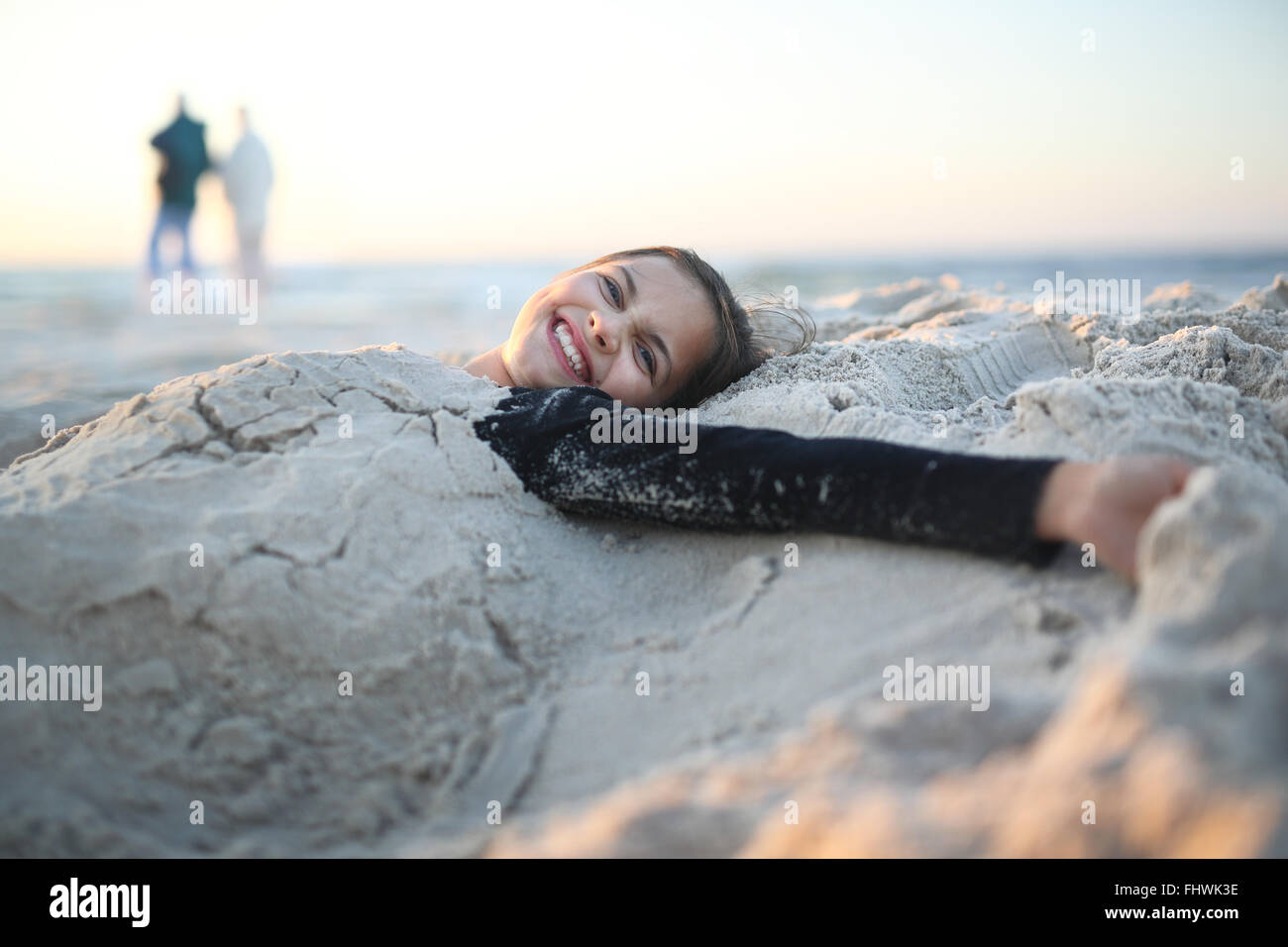 Plage, joie et plaisir. Rire, happy girl lying on a sandy beach Photo Stock